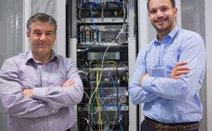 Technicians smiling while standing in front of servers in data center